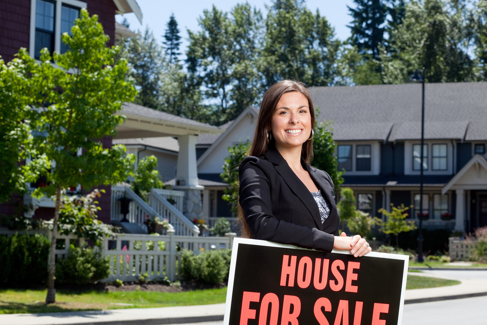 Professionally dressed real estate woman outside with a house for sale sign.