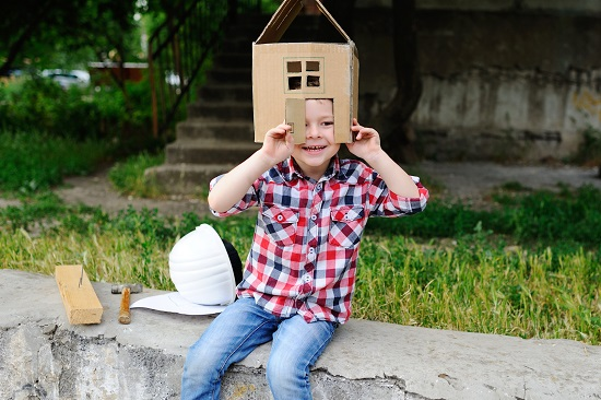 Child playing in a cardboard toy house